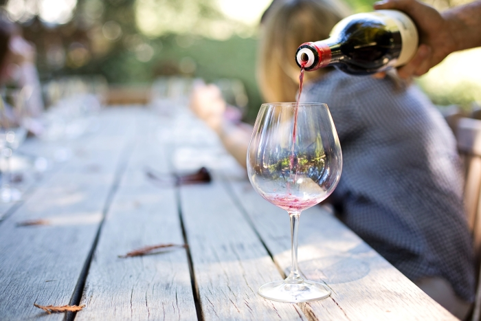 Wine is poured in a glass at one of California's many stunning wine destinations.